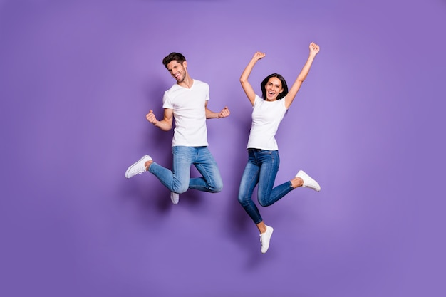 Foto de corpo inteiro de pessoas alegres, animadas, em êxtase positivo, pulando em jeans jeans e calçados brancos que expressam emoções isoladas de fundo de cor violeta pastel