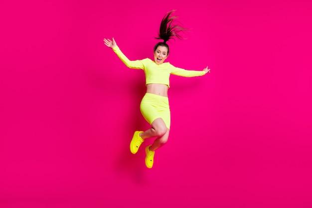 Foto de corpo inteiro de pulando alto gritando energético garota esportiva rindo isolada em um fundo de cor rosa vibrante