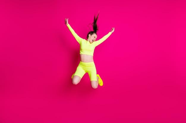 Foto de corpo inteiro de pulando alto gritando esportista energética rindo isolada em um fundo de cor rosa brilhante