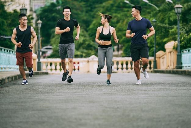Foto de corpo inteiro de quatro pessoas correndo de manhã