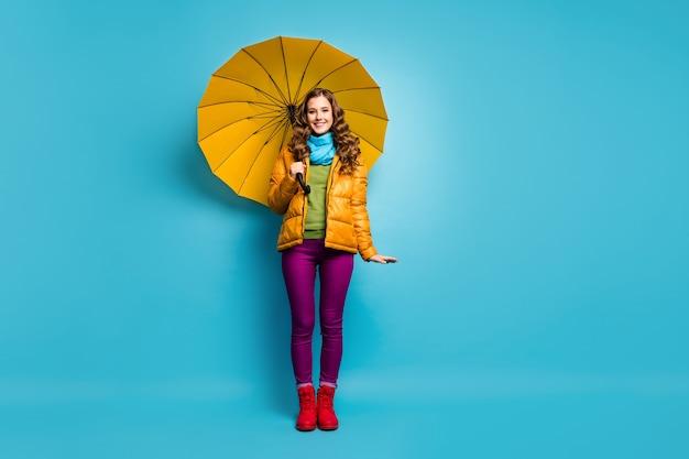 Foto de corpo inteiro de senhora bonita engraçada segurando guarda-chuva brilhante aproveite dia ensolarado de primavera caminhada pela rua no exterior usar casaco amarelo lenço calça violeta sapatos vermelhos parede cor azul