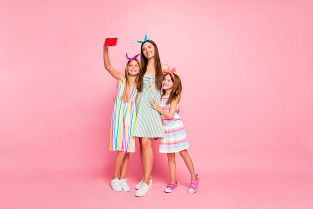 Foto de corpo inteiro de três pessoas fofas com longos cabelos loiros morenos fazendo selfie usando tiaras com vestido de saia isoladas sobre fundo rosa
