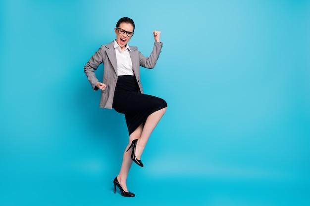 Foto de corpo inteiro de um advogado encantado com os punhos levantados gritando e vestindo jaqueta isolada sobre um fundo de cor azul