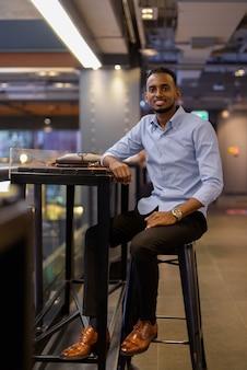 Foto de corpo inteiro de um belo empresário negro africano sentado dentro de um shopping center plano vertical
