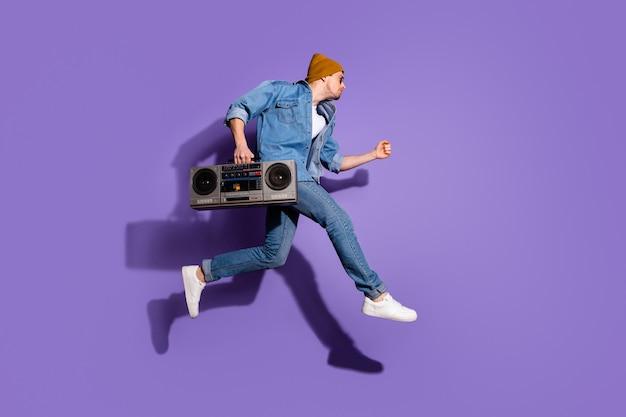 Foto de corpo inteiro de um cara bonito urgente em uma camisa jeans segurando um gravador de áudio retrô com a mão pulando em direção à discoteca isolada sobre um fundo de cor violeta violeta