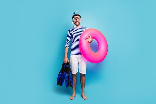 Foto de corpo inteiro de um cara engraçado e animado, turista, nadador, segurando máscara subaquática, tubo de respiração, nadadeiras, bóia salva-vidas rosa usar shorts com camisa de marinheiro listrado isolado cor azul