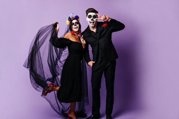 Foto de corpo inteiro de um cara engraçado e uma garota com máscaras de máscaras, rindo e posando de bom humor. senhora de véu preto com flores no cabelo toca o namorado, mostrando o símbolo da paz.