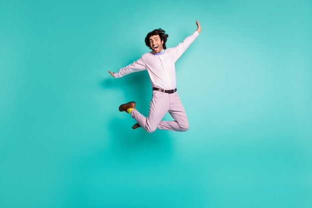 Foto de corpo inteiro de um cavalheiro louco e feliz pulando vestido com uma roupa formal com meias amarelas isoladas em um fundo de cor turquesa