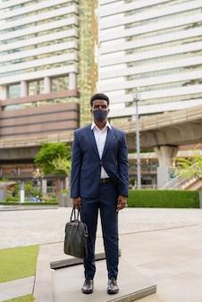 Foto de corpo inteiro de um empresário africano ao ar livre na cidade usando máscara facial