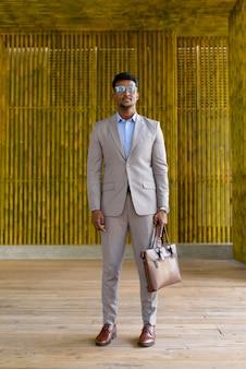 Foto de corpo inteiro de um empresário africano ao ar livre usando óculos