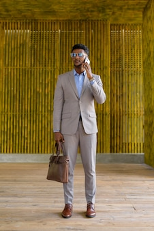 Foto de corpo inteiro de um empresário africano ao ar livre usando telefone celular