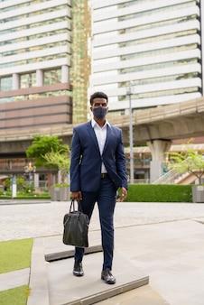 Foto de corpo inteiro de um empresário africano caminhando ao ar livre na cidade usando máscara facial, foto vertical
