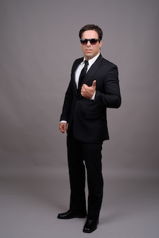 Foto de corpo inteiro de um empresário bonito com óculos escuros