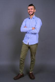 Foto de corpo inteiro de um empresário turco barbudo feliz sorrindo com os braços cruzados