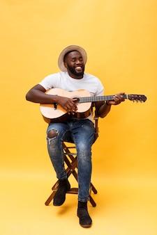Foto de corpo inteiro de um homem artístico animado tocando seu violão em uma suíte casual.