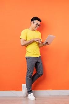 Foto de corpo inteiro de um homem asiático de camisa amarela na parede laranja