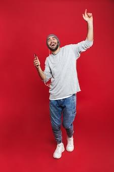 Foto de corpo inteiro de um homem barbudo 30 anos cantando enquanto ouve música com fones de ouvido e telefone celular, isolada