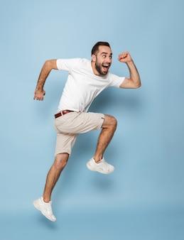 Foto de corpo inteiro de um homem caucasiano alegre em uma camiseta branca casual, regozijando-se e sorrindo enquanto corre isolado na parede azul