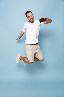 Foto de corpo inteiro de um homem caucasiano com a barba por fazer, em uma camiseta branca casual, pulando e tirando uma selfie no smartphone isolada sobre a parede azul