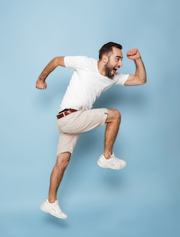 Foto de corpo inteiro de um homem caucasiano feliz em uma camiseta branca casual, regozijando-se e sorrindo enquanto corre isolada na parede azul