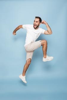 Foto de corpo inteiro de um homem caucasiano otimista em uma camiseta branca casual, regozijando-se e sorrindo enquanto corre isolado na parede azul