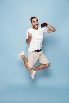 Foto de corpo inteiro de um homem caucasiano positivo em uma camiseta branca casual, pulando e tirando uma selfie no smartphone isolada sobre a parede azul