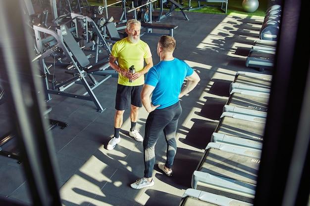 Foto de corpo inteiro de um homem de meia-idade em roupas esportivas conversando com um instrutor de fitness ou pessoal