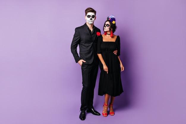 Foto de corpo inteiro de um homem e uma mulher com uma roupa preta elegante e máscaras de halloween, posando na parede roxa.