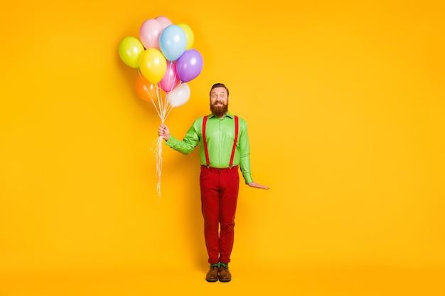 Foto de corpo inteiro de um homem imponente segurando muitos balões para celebrar o aniversário de aniversário, vista uma roupa bonita isolada sobre cores vibrantes