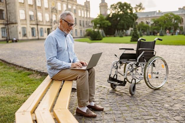 Foto de corpo inteiro de um homem maduro recuperando um paciente com cadeira de rodas trabalhando em um laptop enquanto está sentado