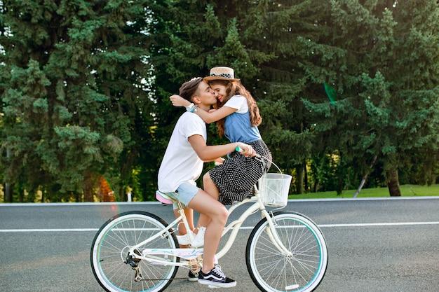 Foto de corpo inteiro de um jovem casal apaixonado em bicicleta na estrada no fundo da floresta. um cara de camiseta branca está dirigindo uma bicicleta e beijando uma garota sentada no guidão