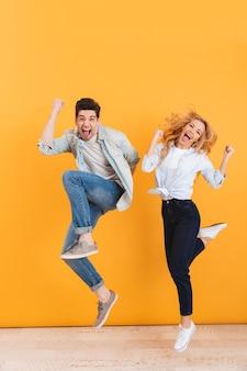 Foto de corpo inteiro de um jovem casal feliz gritando de surpresa enquanto pula e fecha os punhos como vencedores, isolada sobre a parede amarela