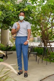 Foto de corpo inteiro de um jovem empresário turista africano ao ar livre, distanciando-se socialmente e usando uma máscara facial para se proteger do covid 19 coronavírus