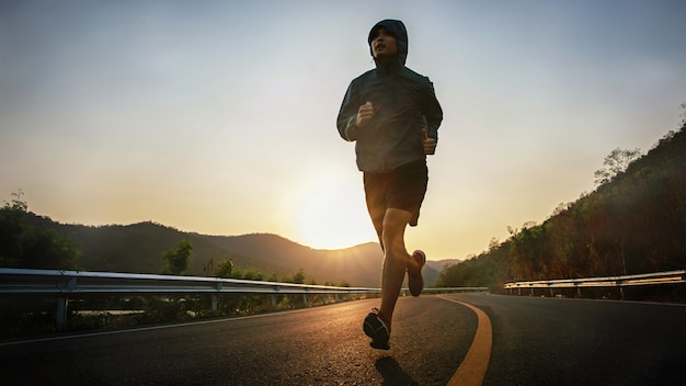 Foto de corpo inteiro de um jovem saudável correndo na estrada de asfalto pela manhã