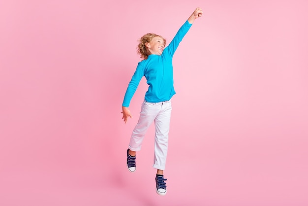 Foto de corpo inteiro de um menino pequeno pulando, levantando o punho, usando tênis de gola alta azul com fundo de cor rosa pastel isolado