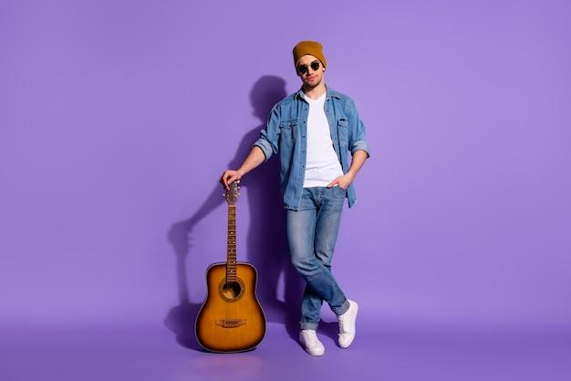 Foto de corpo inteiro de um violão confiante apoiado em sua guitarra usando calçado de tênis branco com boné isolado sobre fundo de cor roxa vibrante projetando sombra