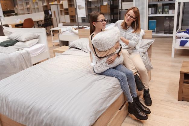 Foto de corpo inteiro de uma adolescente e suas mães sentadas em uma cama nova em uma loja de móveis
