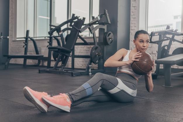 Foto de corpo inteiro de uma adorável desportista exercitando com bola medicinal no ginásio