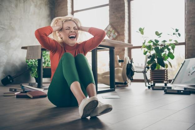 Foto de corpo inteiro de uma agente freelancer frustrada, com mau humor negativo, louca despedida, sentindo-se oprimida, grite, grite, toque o cabelo loiro, sente-se no chão em um escritório bagunçado.