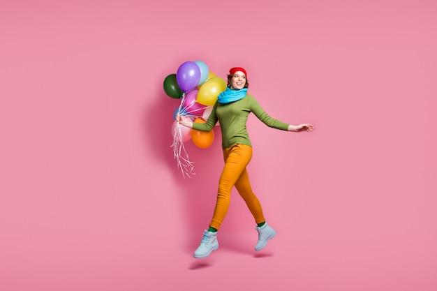 Foto de corpo inteiro de uma alegre garota sonhadora pular segurar muitos balões de bolas de ar olhar copyspace ir caminhar aproveitar a ocasião da primavera usar suéter vermelho isolado sobre a parede cor de rosa
