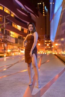 Foto de corpo inteiro de uma bela mulher asiática ao ar livre em bangkok, tailândia, à noite