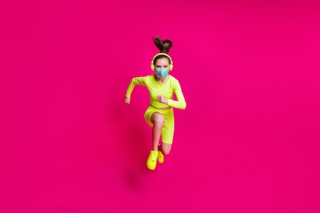 Foto de corpo inteiro de uma corredora pulando alto correndo rápido usando a máscara covid-19 isolada em um fundo de cor fúcsia vibrante