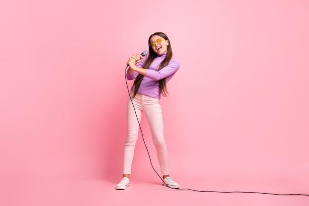 Foto de corpo inteiro de uma criança cantando filho no microfone usando calça violeta isolada sobre fundo de cor pastel