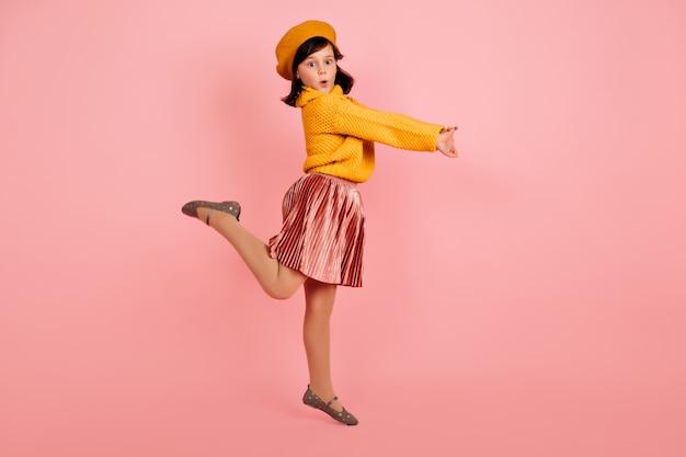 Foto de corpo inteiro de uma criança deslumbrante em pé sobre uma perna. criança despreocupada pulando na parede rosa.