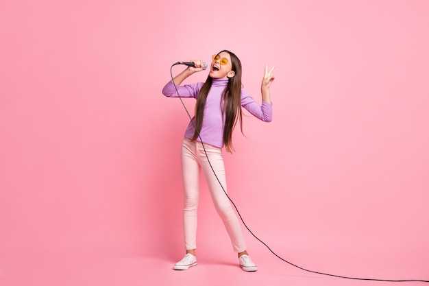 Foto de corpo inteiro de uma criança pequena estrela pop estrela cantando música com um suéter violeta isolado sobre um fundo de cor pastel