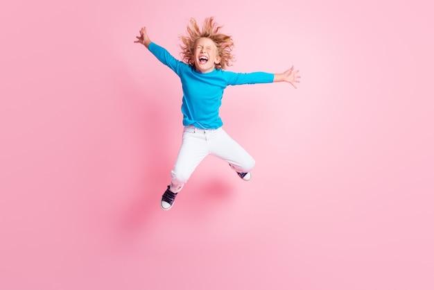 Foto de corpo inteiro de uma criança pequena pulando olhos abertos, boca aberta, calça azul de gola alta, tênis com fundo de cor rosa pastel isolado