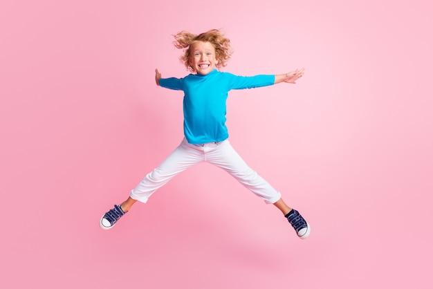 Foto de corpo inteiro de uma criança pequena pulando pernas mãos estrela usar tênis de gola alta azul com fundo de cor rosa pastel isolado