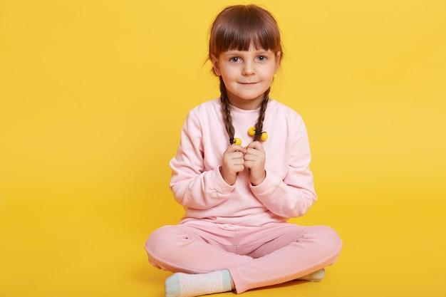 Foto de corpo inteiro de uma criança tímida sentada com as pernas cruzadas