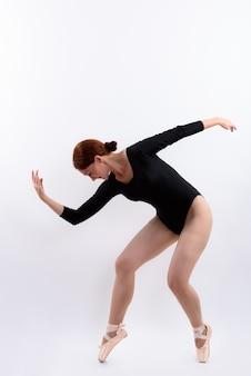 Foto de corpo inteiro de uma dançarina de balé posando isolada contra um fundo branco