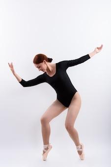 Foto de corpo inteiro de uma dançarina de balé posando nas pontas dos pés, isolada contra um fundo branco